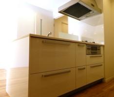 マットなフローリングに艶のある白いキッチン