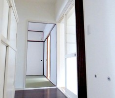 漆喰を思わせるような白い壁の玄関