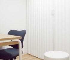 壁同色のアコーディオンカーテンで診察室を区切る