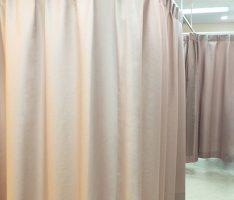 診察ベットの仕切りにはグレイシュなピンクのカーテンを